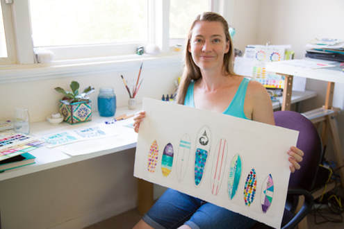 Surf Artist Hannah Katarski with a finished surfboard artwork