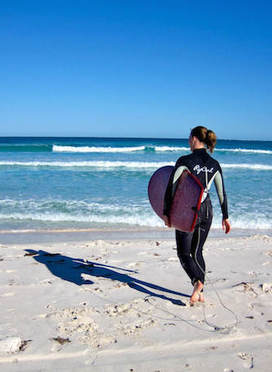 Surfer girl with mini simmons surfboard at the beach in Western Australia